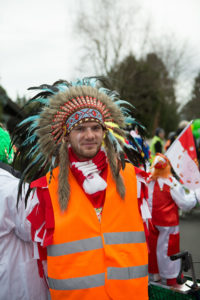 Man dressed up for carnival in cologne, wearing a Indian-head ornament with blue and black feathers and a public workers safety street vest.