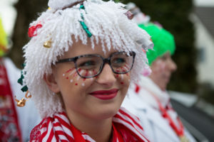Smiling young lady wearing a white clown wig, with red and white lines of make up under her eye and blurred out people in the background.